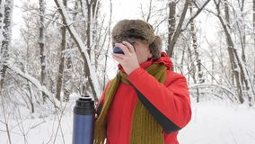 Ederly European man drinking tea from a thermos bottle in a snow-covered forest. Thick dense thicket of trees and roots. In in the snow-covered forest. Hike and stock video footage