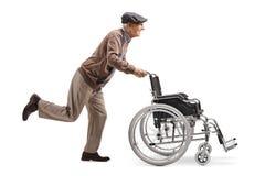 Ederly mężczyzny dosunięcie i bieg pusty wózek inwalidzki zdjęcie stock