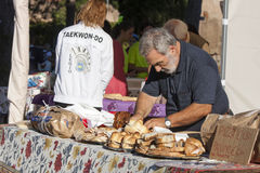 Ederly man preparing pizza with mortadella and porchetta sandwich Royalty Free Stock Photo