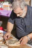 Ederly man som förbereder pizza med mortadella Royaltyfri Fotografi