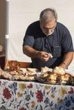 Ederly man som förbereder pizza med mortadella och porchettasmörgåsen Royaltyfri Bild