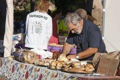 Ederly man som förbereder pizza med mortadella och porchettasmörgåsen Royaltyfri Foto