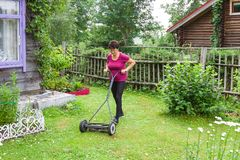 Ederly woman mowing grass with lawn mower in the garden royalty free stock images