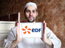 Edf logo. Logo of energy and home services company edf on samsung tablet holded by arab muslim man stock images