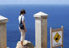 On The Edge. The girl is standing on the edge of a cliff next to the warning sign on Antigua island (Antigua & Barbuda royalty free stock photos