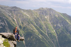 On the edge. Young male is sitting on the edge of a precipice in Tatra Mountains, Slovakia Royalty Free Stock Image