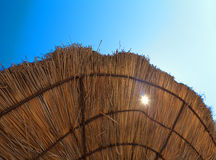 Edge of beach umbrella from dry grass with translucent. Sun on blue sky background Royalty Free Stock Photography