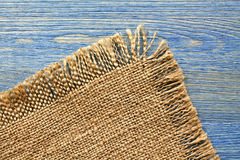 Edge of burlap cloth on a blue  table Royalty Free Stock Photo