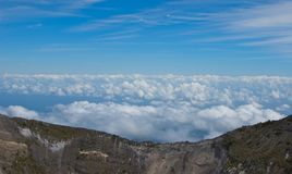 Edge of the Caldera. At an altitude of 11,300 feet, the Irazú Volcano rises above the clouds to reveal an open sky at the edge of the caldera Stock Photos
