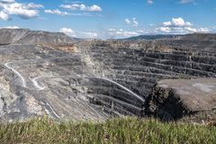View of pit crater from the top. Edge of deep stone quarry at the bright summer noon Royalty Free Stock Photos