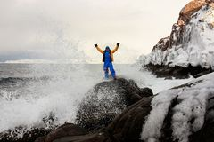 On the edge of earth, north of Russia, Arctic Ocean shore. Contrast of nature and man. Beautiful snowy view of sea shore with. Waves on stony beach, clouds sky stock photo