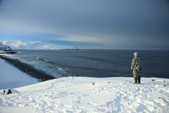 On the edge of the earth, north of Russia, the Arctic Ocean shore. Contrast of overall nature and small man. Beautiful snowy view. Of sea shore with waves on stock photos