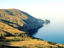 On the edge of the earth. Where earth meets the sea. Cape Meganom in peninsula Crimean Stock Photography