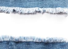 Edge frame of blue denim jeans ripped over white background. Royalty Free Stock Photo
