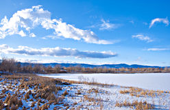 Edge of a Frozen Lake with View of Mountains Royalty Free Stock Image