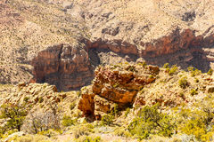 Edge of Grand Canyon. Looking into the gorge of Grand Canyon from the edge of the cliffs. There are some green shrubs growing on the cliffs. The bottom of the Royalty Free Stock Photo