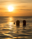Infinity edge pool with sea underneath sunset Stock Photos