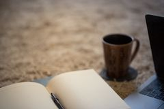 The edge of an inviting open journal with coffee mug and laptop,. Against a mottled warmly lit background of a rug royalty free stock image