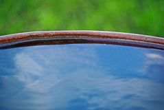 Edge of iron barrel full of water. With blue sky reflection Stock Photo