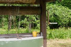 Edge of old well pulley with chain and mottled cup Royalty Free Stock Photography