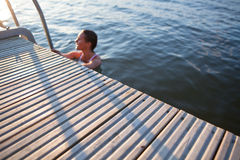 Edge of pier with woman in water Royalty Free Stock Photography