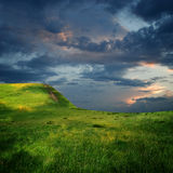 Edge of plateau and majestic clouds. Edge of mountain plateau and majestic sky with clouds over the green hills Stock Image