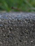 Edge of a retaining wall. The edge of a granite and stone retaining wall with grass in the background Royalty Free Stock Images