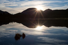 The edge of the rising sun over the mountain and reflection in the lake. Stock Photos