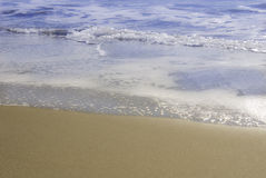 Edge of sea with golden sand. Gentle waves lapping on empty golden sand stock photography