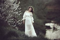 On the edge of the shore near the river there is a girl in a white dress near a flowering tree. The girl in the wind in