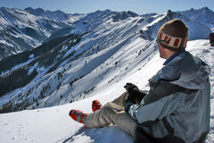 On the edge. Skier on the edge of Highlands Bowl enjoing cup of coffee before the descend, Aspen, Colorado Royalty Free Stock Images
