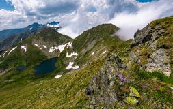 Steep slope on rocky hillside in clouds. Edge of steep slope on rocky hillside in cloudy weather. dramatic scenery with snow near glacier in Fagaras mountains Stock Photography
