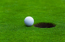 At the edge of success. Picture of a golf ball near the hole Stock Photo
