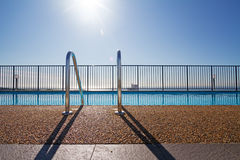 Edge of swimming pool with sun flare in background Stock Images
