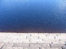 Edge of water. A very calm scene, the wall of a dam and the soothing ripples of the water Royalty Free Stock Image