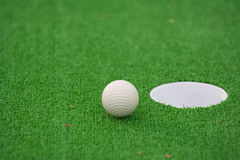 Edge. White golf ball almost in the hole Stock Image