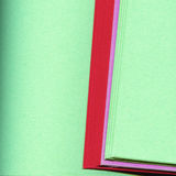 Edges of colored papers. The edges of sheets of red, pink and green colored papers royalty free stock photos