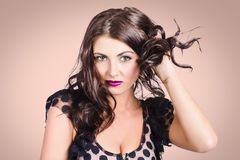 Edgy hair fashion model with brunette hairstyle. Edgy fashion model with sexy style pulling at brunette hair locks while wearing violet lipstick make up Stock Photos