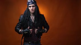 Edgy rocker wearing makeup and bandana, adjusting his leather jacket. Young man with black hair, makeup on his face, and bandana on his head, adjusting his black stock footage
