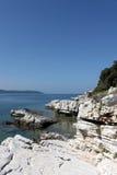 Edgy rocks near Kassiopi beach. Seashore with edgy rocks near Kassiopi beach Royalty Free Stock Photography