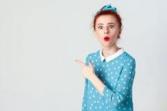 Edheadmeisje in blauwe kleding, die op lege die studiomuur richten, met verkoopprijzen wordt verrast, die haar mond brede open ho royalty-vrije stock foto's