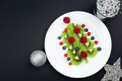 Free Edible Christmas Tree From Kiwi Slices On A Black Plate Over Dark Slate, Stone Or Concrete Background Stock Photo - 131565990