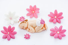 Edible fondant sleeping baby girl and flowers cake topper for de. Coration christening and birthday cake stock photography