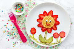 Edible fruit flower - creative summer breakfast or snack for kid. S from fresh strawberry and kiwi shaped smiling flower stock images
