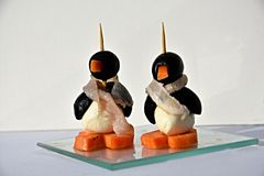 Finger food, funny  edible small penguins. Edible small penguins made from black olives cheese carrots and a  scarf made from ham, hearty in the taste Royalty Free Stock Photos