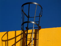 Edifício amarelo, escada preta. Fotos de Stock
