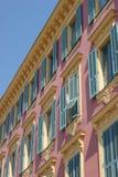 Edifício cor-de-rosa e amarelo com obturadores Fotos de Stock