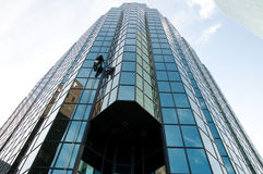 Edifício de vidro moderno que está sendo limpado Fotografia de Stock Royalty Free