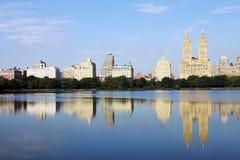 Edifícios de New York City que refletem na água imagem de stock