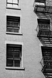 Windows and fire escape. On the side of a brick building in New York City Royalty Free Stock Photos